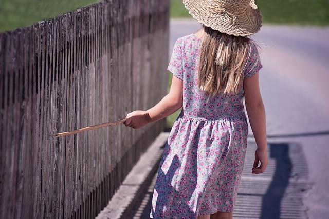 柵を叩きながら歩く子ども
