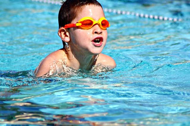 プールで泳ぐ少年